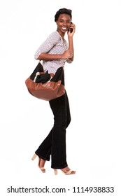 Full length portrait of beautiful african american woman with purse talking on phone