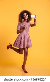 Full length portrait of a beautiful afro american woman in retro style clothes holding lollipop while standing and taking a selfie isolated over yellow background