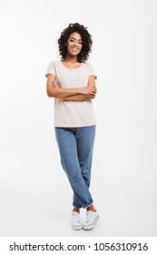 Full length portrait of beautiful american woman wearing jeans and t-shirt standing with arms folded and smile isolated over white background