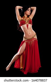 Full length portrait of a beautiful belly dancer wearing a red bellydance costume. She is posing with her hands behind her head. Isolated on black.