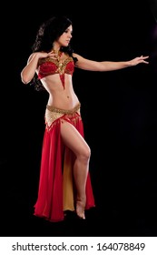 Full length portrait of a beautiful belly dancer wearing a red bellydance costume. She in profile view and posing with one arm extended. Isolated on black.
