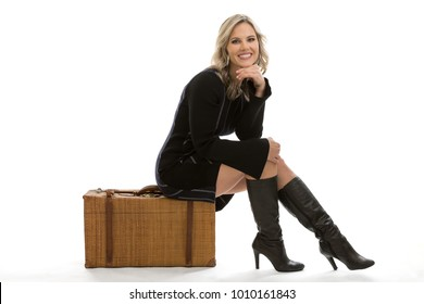 Full length portrait of a beautiful blond mid 30s woman sitting on a vintage rattan suitcase ready for travel, wearing a black vintage style sweater dress and thigh high black boots isolated on white