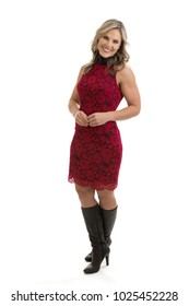 Full length portrait of a beautiful blond mid 30s woman wearing a red lacy dress and thigh high boots isolated on white