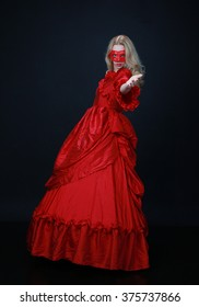 full length portrait of a beautiful blonde woman wearing a red lace mask and a historical red silk, victorian era ball gown.