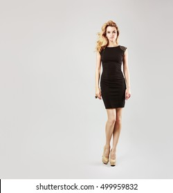 Full Length Portrait of a Beautiful Blonde Woman in Little Black Fashion Dress. Gray Background. Toned Photo with Copy Space.