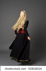 full length portrait of a beautiful blonde woman wearing a black and red medieval gown, standing pose against a grey studio background.