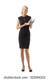 Full length portrait of beautiful business woman standing against white background while holding digital tablet in her hands and working online.