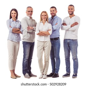 Full length portrait of beautiful business people in smart casual wear looking at camera and smiling while standing with folded arms on a white background
