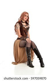 full length portrait of a beautiful girl wearing steampunk outfit, seated pose isolated on white background.