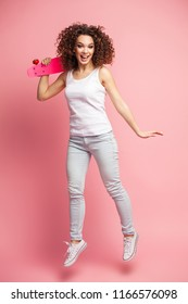 Full length portrait of a beautiful happy woman in summer clothes posing and looking away while jumping and holding skateboard isolated over pink background