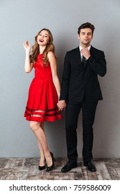 Full length portrait of a beautiful happy couple dressed in formal wear posing while holding hands and looking at camera over gray wall background