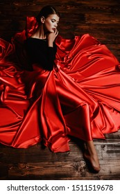 A full length portrait of a beautiful lady in a long red skirt lying on a wooden floor. Beauty, fashion. Latino dance.