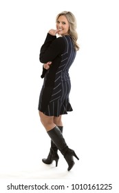 Full length portrait of a beautiful mid 30s blond woman wearing a black retro sweater dress and thigh high boots, looking over shoulder isolated on white background