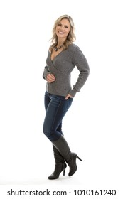 Full length portrait of a beautiful mid 30s casual blond woman wearing a sweater, jeans and high heel boots isolated on a white background with hand in back pocket