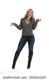 Full length portrait of a beautiful mid 30s blond woman wearing a sweater, jeans and high heel boots, with hands in the air wondering, isolated on a white background