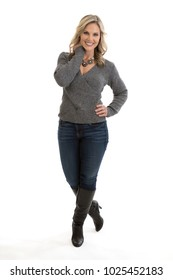 Full length portrait of a beautiful mid 30s blond woman wearing a sweater, jeans and high heel boots, hands on hips, isolated on a white background