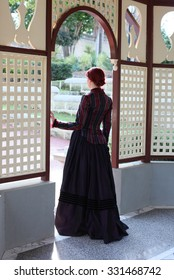 Full Length Portrait of a beautiful red haired girl wearing  Gothic inspired Victorian era clothes. walking through a doorway, rear view.