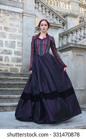 Full Length Portrait of a beautiful red haired girl wearing  Gothic inspired Victorian era clothes. walking down a stone castle staircase.