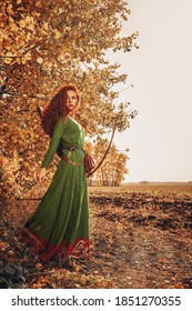 Full length portrait of a beautiful red-haired girl archer of the Middle Ages stands next to the autumn forest. Celtic culture. Fantasy world.