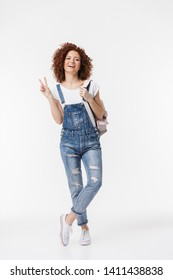 Full length portrait of beautiful redhead curly woman 20s wearing denim jumpsuit smiling and looking at camera isolated over white background