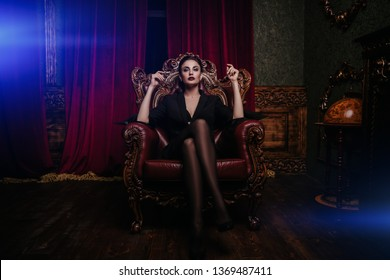 A full length portrait of a beautiful sexy woman wearing a black blazer and posing in classic interior on the armchair. Fashion, style, beauty, interior.