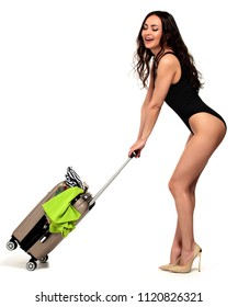 Full length portrait of a beautiful smiling happy young woman in a black swimsuit pulling a suitcase, isolated on a white background, summer vacations concept