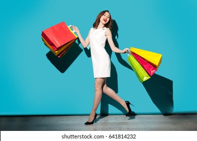 Full length portrait of a beautiful smiling woman in dress walking with colorful shopping bags isolated over blue background