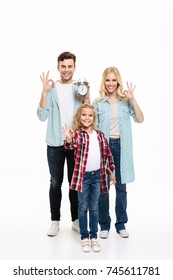 Full length portrait of a beautiful smiling family with a child holding alarm clock and showing ok gesture isolated over white background