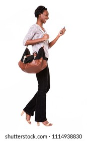 Full length portrait of beautiful tall african american woman with purse and smart phone