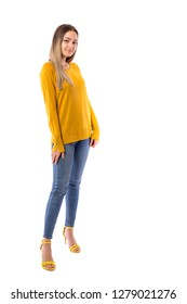 Full length portrait of a beautiful teenage girl wearing jeans and yellow sweater posing over white background