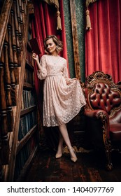 A full length portrait of a beautiful woman posing in the interior near the armchair. Interior, fashion.