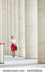 Full length portrait of beautiful woman wearing red skirt walking towards camera along row of pillars, copy space