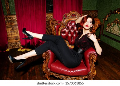 A full length portrait of a beautiful woman posing in the vintage interior on the leather armchair and wearing elegant clothes. Beauty, fashion, interior.