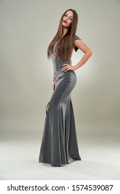 Full length portrait of a beautiful woman in long glittering dress, studio shot