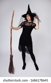 full length portrait of beautiful woman in black witch halloween costume with broom over white background