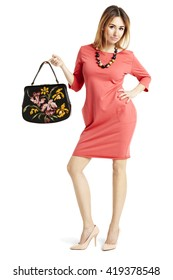 Full length portrait of beautiful woman in a red dress. She holding a bag.