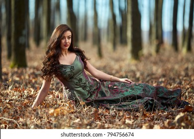 Full length portrait of a beautiful woman in green dress outdoor