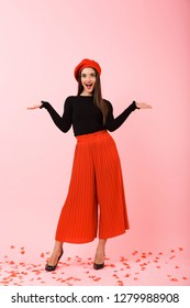 Full length portrait of a beautiful young woman wearing red beret standing isolated over pink background, presenting copy space