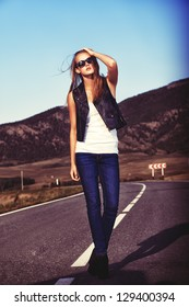 Full length portrait of a beautiful young woman posing on a road over picturesque landscape.