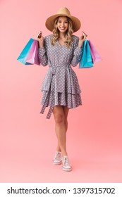 Full length portrait of a beautiful young blonde woman wearing summer straw hat standing isolated over pink background, holding shopping bags