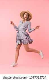 Full length portrait of a beautiful young blonde woman wearing summer straw hat jumping isolated over pink background, posing