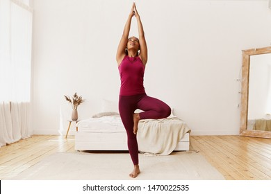 Full length portrait of beautiful young Afro American woman with fit healthy body raising hands and placing sole of foot on her thigh, doing tree yoga stance or vriksasana in cozy bedroom interior