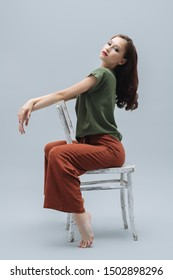 A full length portrait of a beautiful young woman with the chair over the grey background in the studio. Casual fashion.