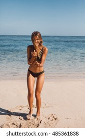 Full length portrait of beautiful young woman having fun on the beach vacation. Female model wearing bikini enjoying on the sea shore.