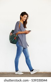Full length portrait of beautiful young woman walking outside and reading text message on her mobile phone