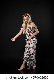 full length portrait of a beautiful young lady with long blonde hair wearing a floral dress and crown of flowers.  isolated against a black studio background.