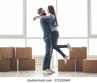 Full length portrait of beautiful young couple hugging and smiling while standing among moving cardboard boxes