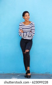 Full length portrait of beautiful young black woman smiling against blue wall in striped shirt