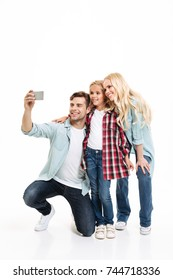 Full length portrait of a beautiful young family with a child standing together and taking a selfie isolated over white background