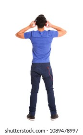 Full length portrait from behind of a man wearing headphones to listen music over white background
